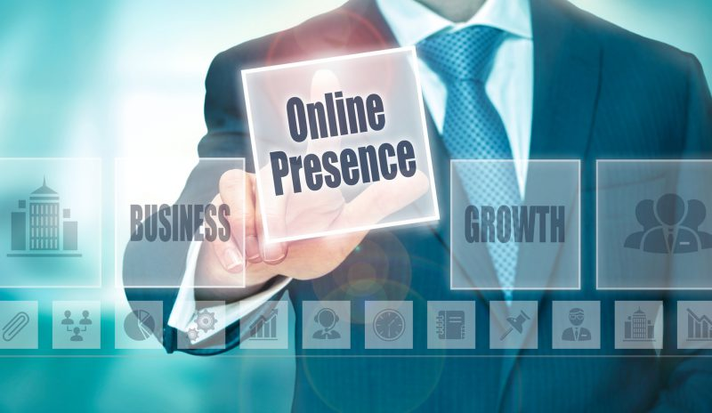 A businessman selecting a Online Presence Concept button on a clear screen.